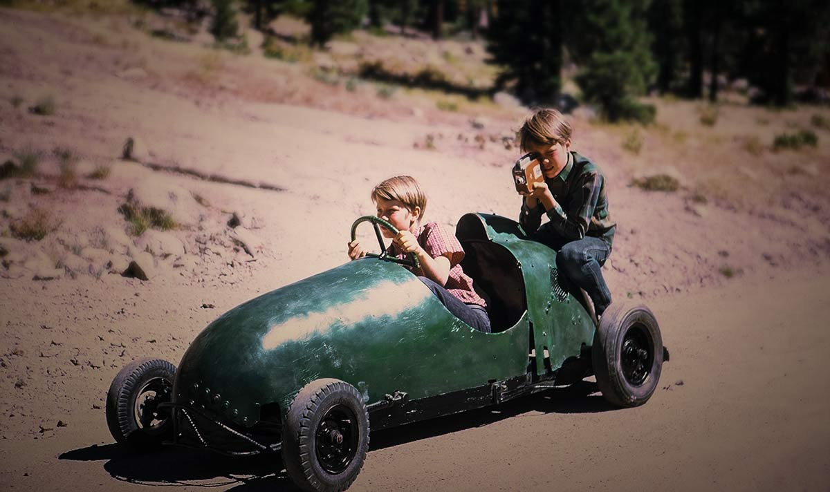 brothers on a down hill racer with super8 camera